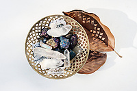 Metal basket filled with magical crystal healing stones and two Magnolia leaves.