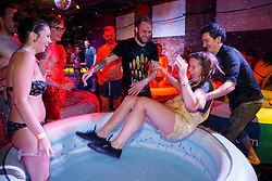 © Licensed to London News Pictures. 07/06/2014. LONDON, UK. People throwing a bartender into a hot tub as they attend 'Hot Tub Underground Cinema' at former Shoreditch Underground station in east London on Saturday, 8 June 2014. Visitors of the unique cinema enjoy a Jacuzzi with friends during classic films such as Moulin Rouge and Snatch. Photo credit : Tolga Akmen/LNP