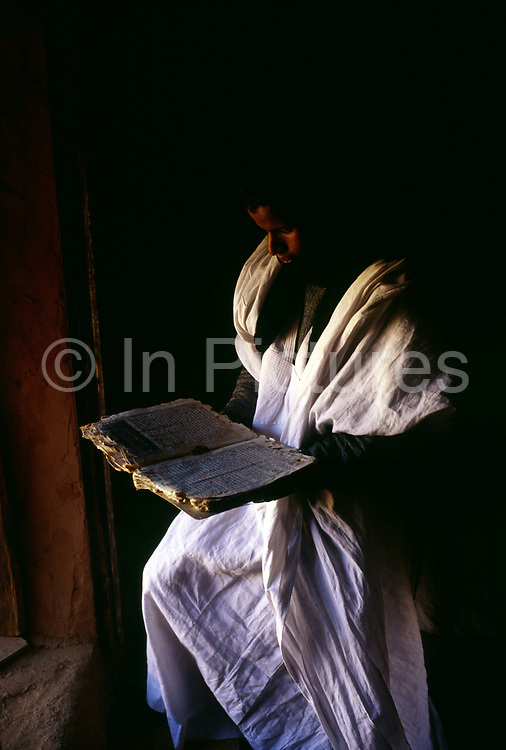 """A librarian in an ancient library, reads an ancient book in Chinguetti. One of Islam's holiest cities (today it is regarded as the seventh holiest city) it has been dated at a around seven hundred, (700) years old and is famed for it's Koranic libraries and distinctive mosque, Mauritania. From the story """"The Wind and the City""""."""