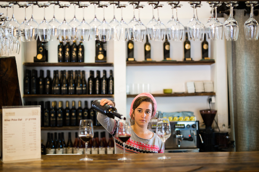 Jewish Israeli worker Naomi Vaknin is seen as she pours wine to glasses at Psagot Winery in the West Bank Jewish settlement of Migron, near the Palestinian West Bank city of Ramallah, on November 17, 2015.