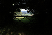 View over agricultural farmland through trees and over an old farm gate near Dorstone in the Golden Valley, Herefordshire, United Kingdom. The Golden Valley is the name given to the valley of the River Dore in western Herefordshire, England. The valley is a picturesque area of gently rolling countryside.