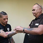 The Center Orlando executive director Terry DeCarlo (R) places a bracelet on professional boxer Orlando Cruz of Puerto Rico after he pays his respects to the victims of the Pulse Nightclub shooting on Tuesday, July 12, 2016 in Orlando, Florida. Cruz, who lost four friends in the tragic incident was the first openly gay boxer in the sport and will fight for his fifth time in the Orlando area this Friday.  (Alex Menendez via AP)