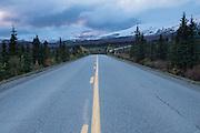 Park road heading toward mountains and sotrm clouds, Denali National Park, Alaska