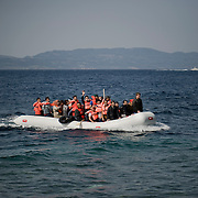 A group of Syrian refugees on a small inflatable boat minutes before their landing on the beach of Skala Sykaminias. In the horizon the Greek Coast Guard vessel could be seen. Everyday hundreds of refugees, mainly from Syria and Afghanistan, are crossing in small overcrowded inflatable boats the 6 mile channel from the Turkish coast to the island of Lesbos in Greece. Many spend their life savings, over $1000, to buy a space on those boats.