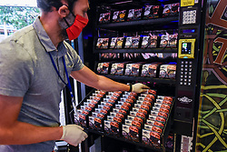 © Licensed to London News Pictures. 22/06/2020. LONDON, UK. A staff member loads a vending machine in Carnaby Street selling facemasks to the public by London-based company Maskey.  Established by entrepeneur Adam Freeman to address the demand for affordable UK-made facemasks during the ongoing coronavirus pandemic, the newly established company is installing the UK's first fashionable face mask vending machines in locations around London, with plans to expand further.  10% of the profit from each facemask sale is donated to a charity supporting the NHS.  Photo credit: Stephen Chung/LNP