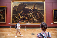 A woman alone is watching The raft of the Medusa of Gericault at Louvre Museum.