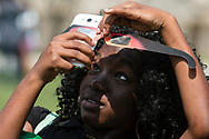 Middletown, New York - A woman takes a cell phone photograph while using eclipse glasses to watch a partial solar eclipse on Alumni Green at SUNY Orange on Aug. 21, 2017.