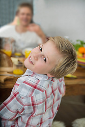 Portrait of smiling boy at home, his father in the background