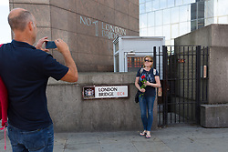 """© Licensed to London News Pictures. 11/06/2017. LONDON, UK.  A woman poses for a photograph with a red rose on London Bridge this afternoon. 1,000 red roses with messages of """"love and solidarity"""" were given to passers by on London Bridge today.  Photo credit: Vickie Flores/LNP"""