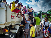 """22 JANUARY 2018 - CAMALIG, ALBAY, PHILIPPINES: People who live on the slopes of the Mayon volcano get out of a government truck after their arrival at an evacuation center. There were a series of eruptions on the Mayon volcano near Legazpi Monday. The eruptions started Sunday night and continued through the day. At about midday the volcano sent a plume of ash and smoke towering over Camalig, the largest municipality near the volcano. The Philippine Institute of Volcanology and Seismology (PHIVOLCS) extended the six kilometer danger zone to eight kilometers and raised the alert level from three to four. This is the first time the alert level has been at four since 2009. A level four alert means a """"Hazardous Eruption is Imminent"""" and there is """"intense unrest"""" in the volcano. The Mayon volcano is the most active volcano in the Philippines. Sunday and Monday's eruptions caused ash falls in several communities but there were no known injuries.    PHOTO BY JACK KURTZ"""