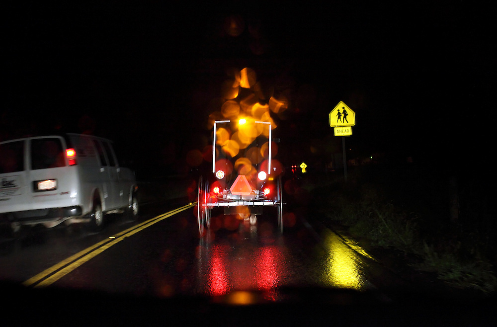 Cars and trucks pass a horse and buggy on a rainy evening outside Berlin, Ohio, Oct. 10, 2009.