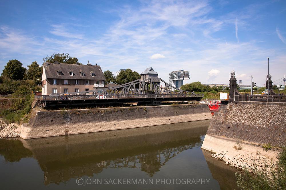 the opened pivot bridge at the harbor in the district Deutz, in the background one of the Crane Houses at the Rhineau harbor, Cologne, Germany.<br /> <br /> die geoeffnete Drehbruecke im Deutzer Hafen, im Hintergrund eines der Kranhaeuser im Rheinauhafen, Koeln, Deutschland.