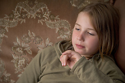 Young girl sitting on the sofa at home watching television,