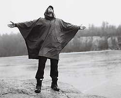 Man in a rain slicker with outstretched arms in the rain