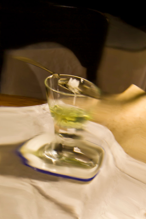 Distorted view of solo absinthe glass with spoon and sugar cube,
