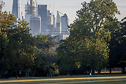 With the skyline of the capitals financial district, the City of London in the distance, a woman does lunges in Ruskin Park, on 10th August 2018, in London, England.