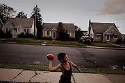 BETHLEHEM, PA – JUNE 14, 2011: Hector Ortiz, age 9, tosses a football to his uncle John Veanus near their home at 430 Grandview in Bethlehem's Northside. Hector, who is one-half Puerto Rican, is one of many Hispanic children whose families have moved out of the poorer Southside and into the middle class white neighborhoods of the Northside, across the Lehigh River.<br />