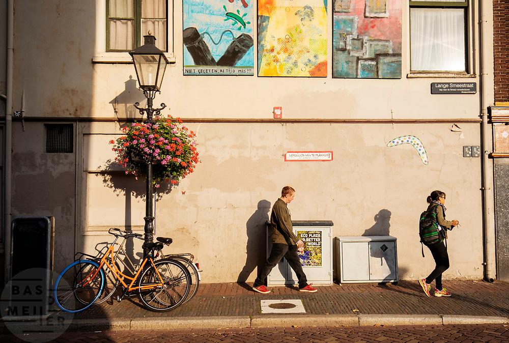 Een man en vrouw lopen door de Lange Smeestraat in Utrecht.<br /> <br /> A man and woman walk in the city center of Utrecht.