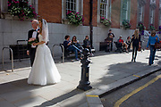 People watch a bride and a male figure before her civil wedding ceremony at Chelsea Registry Office. The mid-afternoon ceremony is due to take place soon and the wedding bridal group have stopped in the street to pose for pictures, the light from behind shines on the bride's white dress. Others look on from benches in the shade, amused and entertained by the formality and prosperity of those taking part.