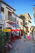Mother and child hold hands as they explore the village of Scopello, Sicily, Italy