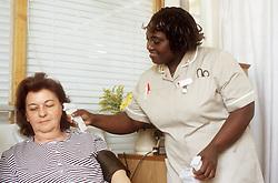 Female nursing auxiliary taking patient's temperature,