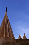 A man stands dwarfed by several Yezidi temples in a village near Mosul in Iraq.<br /> The Yezidi are a mostly Kurdish speaking people's who's religion has long been seen, mistakenly, as having elements of devil worship. Their faith at times heavily persecuted in Iraq is highly synchretic and has elements of Sufistic Islam as well as Blblical and Persian influences.