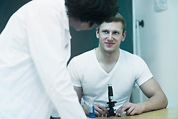 Young college student with microscope and discussing with his teacher in laboratory, Freiburg im breisgau, Baden-Württemberg, Germany