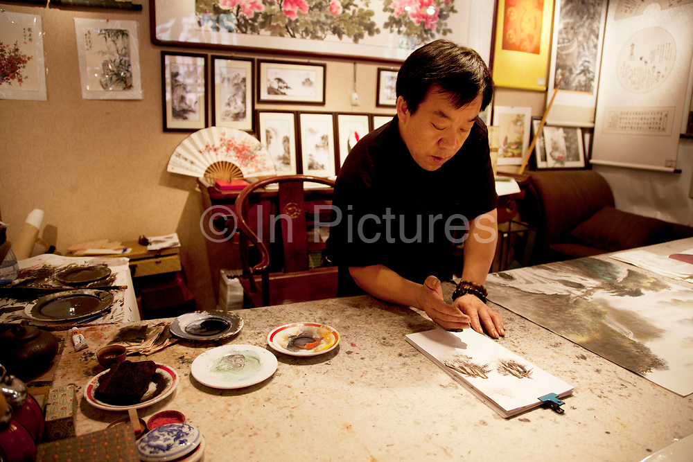 Artist making traditional Chinese paintings, but using various parts of his hand instead of a paintbrush in a studio inside the Forbidden City, the Chinese imperial palace from the Ming Dynasty to the end of the Qing Dynasty. It is located in the middle of Beijing, China, and now houses the Palace Museum. For almost 500 years, it served as the home of emperors and their households, as well as the ceremonial and political center of Chinese government. Built in 1406 to 1420, the complex consists of 980 buildings. The palace complex exemplifies traditional Chinese palatial architecture, and has influenced cultural and architectural developments in East Asia and elsewhere. The Forbidden City was declared a World Heritage Site in 1987, and is listed by UNESCO as the largest collection of preserved ancient wooden structures in the world.