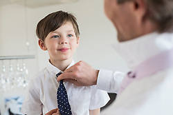 Father adjusting son's tie, smiling