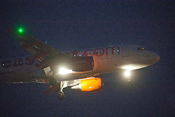Easyjet plane on approach to Edinburgh Airport in the early evening light.