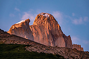 """Sunrise view of Mount Fitz Roy (3405 m or 11,171 ft elevation) and Aguja Guillaumet (left) from Refugio Piedra del Fraile. We hiked the scenic Rio Electrico Valley to Refugio Piedra del Fraile (""""Stone of the Friar"""", 14.5 km round trip) and slept overnight in a basic 4-person dorm room using our sleeping bags carried to use on their pads. Monte Fitz Roy is also known as Cerro Chaltén, Cerro Fitz Roy, or Mount Fitz Roy. The first Europeans recorded as seeing Mount Fitz Roy were the Spanish explorer Antonio de Viedma and his companions, who in 1783 reached the shores of Viedma Lake. In 1877, Argentine explorer Francisco Moreno saw the mountain and named it Fitz Roy in honour of Robert FitzRoy who, as captain of HMS Beagle, had travelled up the Santa Cruz River in 1834 and charted large parts of the Patagonian coast. Mt Fitz Roy was first climbed in 1952. Cerro is a Spanish word meaning hill, while Chaltén comes from a Tehuelche word meaning """"smoking mountain"""", due to clouds that usually form around the peak."""