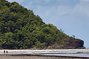 A couple walk along Myall Beach by Cape Tribulation, named by Captain Cook, Queensland, Australia