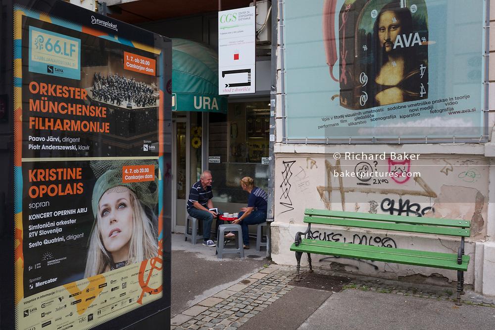 Two people chat outside a cafe in the Slovenian capital, Ljubljana, on 28th June 2018, in Ljubljana, Slovenia.
