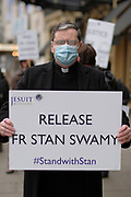 "A priest from ""Jesuit Mission"" hold placards outside Indian High Comission in London to protest against arrest of Father Stan Swamy on Thursday, Dec 10, 2020. <br /> The National Investigation Agency (NIA), which deals with anti-terror crimes, arrested him in connection over a 2018 incident of caste-based violence and alleged links with Maoists. The 83-year-old activist and Jesuit priest is now the oldest person to be accused of terrorism in India. (VXP Photo/ Gio Strondl)"