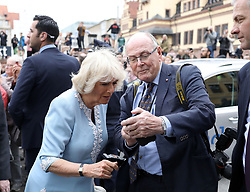 Royal Sun photographer Arthur Edwards shows the Duchess of Cornwall an image of Prince Harry's new baby on his phone during the visit to Leipzig City Hall on the second day of their tour of Germany.