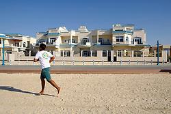 Man jogging past luxury villas facing onto beach in Dubai United Arab Emirates