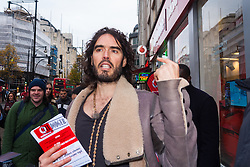Oxford Street, London, December 5th 2014. Actor and Comdeian turned political activist Russel Brand visits several big brands'  stores including Boots, Apple and Vodafone in London accusing them of dodging tax whilst those most in need of benefits are facing cuts and increased hardship. A leaflet being distributed by him claims £14 billion is lost every year, through tax avoidance and loopholes exploited by big business. PICTURED: Russel Brand tells people about Vodafone's alleged tax avoidance and its implications for those on benefits.