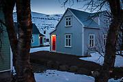 Seyðisfjörður, Iceland, 3 apr 2019, red door in a blue winter landscape.