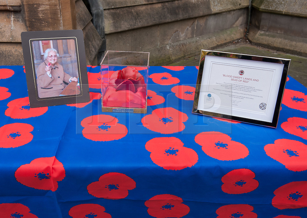 © Licensed to London News Pictures. 23/10/2015. Bristol, UK.  23/10/2015. Bristol, UK. Relatives of Bristol Poppy seller Olive Cooke at an event outside Bristol Cathedral, organised by the Royal British Legion, receive a ceramic poppy in memory of Olive from the Blood Swept Lands and Seas of Red exhibition. Photo credit : Simon Chapman/LNP
