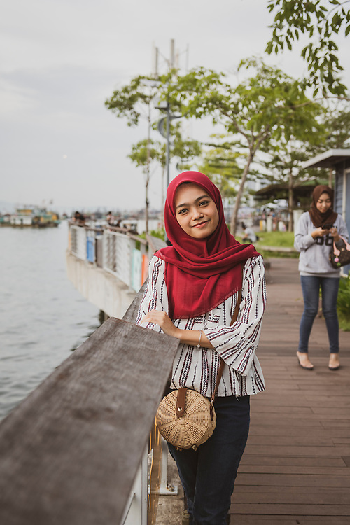 Ain, age 23, at the waterfront in Kota Kinabalu, Sabah, Malaysia. Her friend Hasmina is in the background. (August 9, 2019)