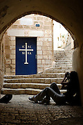 Israel, Tel Aviv, Jaffa, people in a Narrow alleyway next to the door to the Greek Orthodox Church