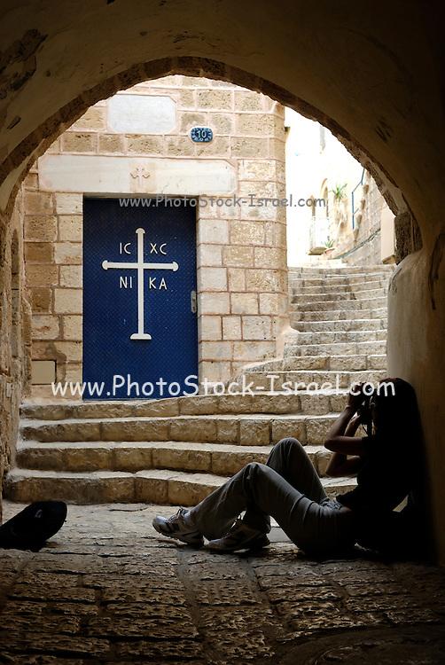 Israel, Tel Aviv, Jaffa, people in a Narrow alleyway next to the door to the Greek Orthodox Church