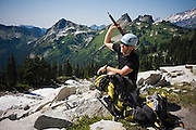 Climber Ian Derrington scratches his back with his ice axe during a traverse of the Tatoosh Range in Mount Rainier National Park, Washington.