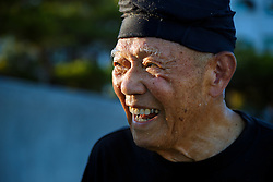 "Ninety-one-year-old Fumiyasu Yamakawa laughs during his morning exercises at the beach near his home in Naha, Okinawa. ""You have vitamin C, we have Vitamin S, for smile,"" he jokes. ""It's very important for a long life."""