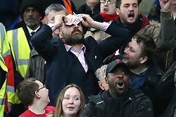 10 January 2018 - Football League Cup - Chelsea v Arsenal - An Arsenal fan mocks the affluence of Chelsea FC by rubbing £50 notes on his head - Photo: Charlotte Wilson / Offside