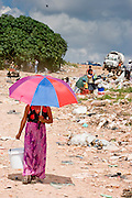 09 NOVEMBER 2004 - TAPACHULA, CHIAPAS, MEXICO: A woman walks through the municipal garbage dump in Tapachula, Chiapas, Mexico, while a garbage truck drives in. About 130 people, the poorest of the poor in Tapachula, work in the dump picking through the garbage hoping to find tidbits they can use or sell to brokers who sit on the edge of the dump and resell the garbage. Most of the dump workers are Guatemalan migrants who crossed the border hoping, at one time, to get to the United States. Now they have settled for an existence on the very edge of Mexican society. PHOTO BY JACK KURTZ