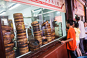 Children watch famous Nanxiang steamed buns being made in Yu Gardens bazaar Shanghai, China