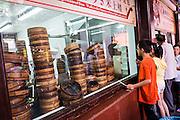 Children watch famous Nanxiang steamed buns being made in Yu Gardens bazaar Shanghai, China