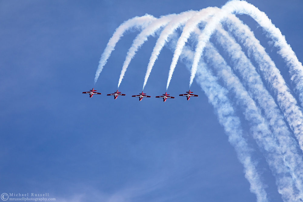 Canadian Forces Snowbirds completing a loop in the Five Line Abreast formation with smoke.  The Snowbirds are also known as the 431 Air Demonstration Squadron and fly the Canadair CT-114 Tutor jet. Photographed during the Canada 150 celebrations in White Rock, British Columbia, Canada.