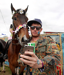 A festivalgoer takes a selfie with police horse Sedgemoor at Glastonbury Festival, at Worthy Farm in Somerset.